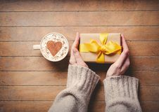 Female hands holding gift box and cup of coffee stock images