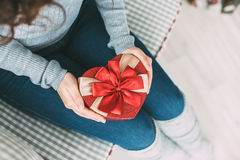 Female hands holding gift box heart. Stock Photos