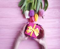 Female hands holding a gift box present birthday , romantic a bouquet of tulips on a wooden background. Female hands holding   gift box, a bouquet of tulips on a stock image
