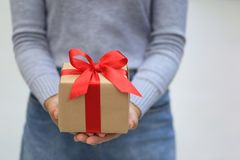 Female hands holding gift box with red ribbon for Christmas and royalty free stock photography