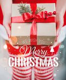 Female hands holding gift box with red ribbon and Merry Christmas and New Year typographical on shiny xmas background. Royalty Free Stock Images