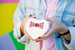 Female hands holding gift box in shape of heart in her hands on. Multicolored background. Romantic banner for Valentine's day royalty free stock photo