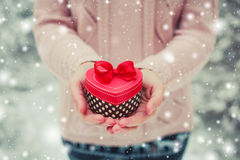 Female hands holding a gift box. Shaped of heart. The Valentines day and Christmas theme Royalty Free Stock Image