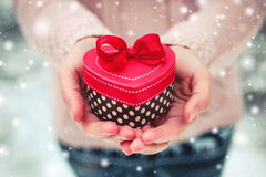 Female hands holding a gift box. Shaped of heart. The Valentines day and Christmas theme Stock Image