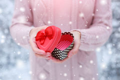 Female hands holding a gift box. Shaped of heart. The Valentines day and Christmas theme Royalty Free Stock Photography