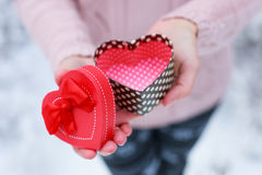 Female hands holding a gift box. Shaped of heart. The Valentines day and Christmas theme Stock Photo