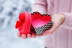 Female hands holding a gift box. Shaped of heart. The Valentines day and Christmas theme Royalty Free Stock Photos