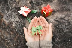 Female hands holding gift box on stone stock photography
