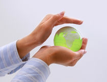 Female hands holding glass earth , isolated on Royalty Free Stock Photos