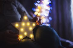 Female hands holding glowing white LED star with warm bokeh background indoor at home. Festive Christmas illumination, holiday atmosphere stock image