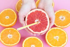 Female hands holding half of a juicy ripe red grapefruit with a straw above oranges stock images