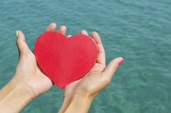 Female hands holding a heart above the sea water. Female hands holding a paper heart above the clear sea water royalty free stock photos