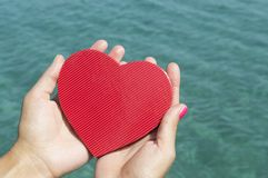 Female hands holding a heart above the sea water Royalty Free Stock Images