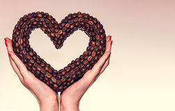 Female hands holding a heart of the coffee beans. Valentine's Day. Woman's day. March 8. Theme of love, romance, coffee time, cafe royalty free stock photos