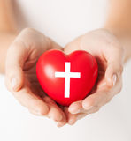 Female hands holding heart with cross symbol. Religion, christianity and charity concept - female hands holding red heart with christian cross symbol stock photo