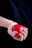 Female Hands Holding a Heart. In a dark background Stock Images