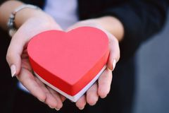 Female hands holding heart shaped gift box. Stock Photography