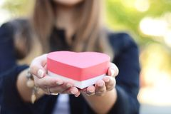 Female hands holding heart shaped gift box. Close up shot of female hands holding heart shaped gift box. Valentines day, romance concept royalty free stock photos