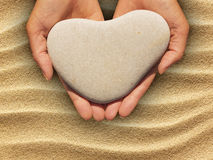 Female hands holding a heart-shaped stone. Female hands holding a natural heart-shaped stone in cupped palms over a background of water worn pebbles stock photo