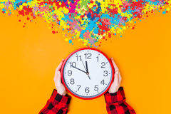 Female hands holding huge clock with color inpiraton Stock Photography