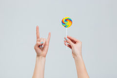 Female hands holding lollipop and showing devil sign. Isolated on a white background Royalty Free Stock Photo