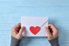 Female hands holding a love letter. Female hands holding a love letter on blue wooden background. Copy space. Red heart. Top view stock photos