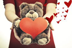 Female hands holding magical heart and soft toy. Valentine's day concept. Female hands holding magical heart and soft toy royalty free stock image