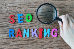 Female hands holding magnifying glass and arrange colorful alpha. Bets SEO RANKING on wooden table as SEO Search engine optimisation concept Stock Photos