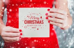 Female hands holding Merry Christmas`s card or letter to Santa. royalty free stock images