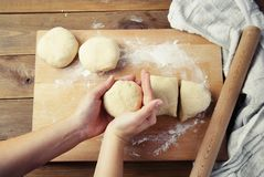 Female Hands Holding and mixing Dough for baking pie, or pizza. Homemade Preparing Food. Top view. Rustic background. stock images