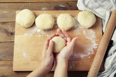 Female Hands Holding and mixing Dough for baking pie, or pizza. Homemade Preparing Food. Top view. Rustic background. stock photos