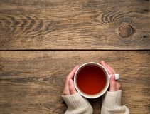 Female hands holding a mug of hot black tea. Cold winter white w. Arm clothes. Top view. Aged rustic wooden background royalty free stock image