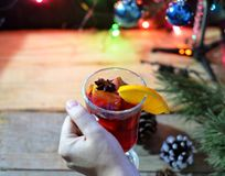 Female hands holding mug with mulled wine above wooden table. Top view.  stock image