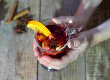 Female hands holding mug with mulled wine above wooden table. Top view.  royalty free stock images