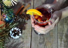 Female hands holding mug with mulled wine above wooden table. Top view.  royalty free stock photos