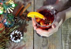 Female hands holding mug with mulled wine above wooden table. Top view.  royalty free stock photography
