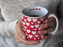 Female Hands holding Mug With Red and WhiteHeart Motif Stock Images