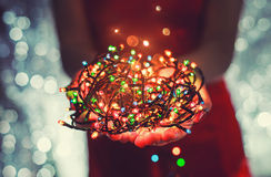 Female hands holding Multicolored Christmas light decorations on dark holiday background. Xmas and New Year theme. Toning Royalty Free Stock Photography