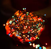 Female hands holding Multicolored Christmas light decorations on dark holiday background. Xmas and New Year theme. Stock Photo
