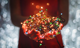 Female hands holding Multicolored Christmas light decorations on dark holiday background. Xmas and New Year theme. Stock Images