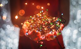 Female hands holding Multicolored Christmas light decorations on dark holiday background. Xmas and New Year theme. Royalty Free Stock Photo