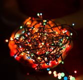 Female hands holding Multicolored Christmas light decorations on dark holiday background. Xmas and New Year theme. Royalty Free Stock Image