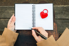 Female Hands holding notebook with closed red padlock in heart s. Hape and pencil stock images