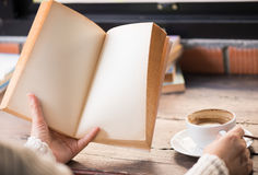 Female hands holding old opened book . Stock Photos