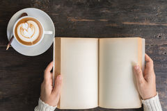 Female hands holding old opened book . Royalty Free Stock Images