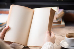 Female hands holding old opened book . Royalty Free Stock Photos