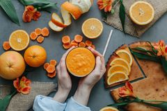 Female hands holding orange smoothie decorated with alstroemeria with orange pie Stock Photo