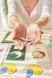 Female Hands Holding Origami Crane. Hands of unrecognizable woman holding small origami crane, table surface with handmade greeting cards on background royalty free stock photography