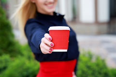 Female hands holding paper cup, closeup. Happy and smiling woman showing  cup with coffee, sunny day.coffee break Stock Photo