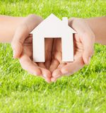 Female hands holding paper house. Real estate and accomodation concept - closeup picture of female hands holding paper house Royalty Free Stock Photo